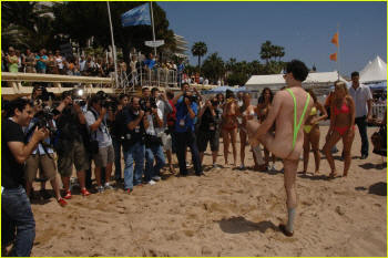 Borat performs for the crowd in his neon lime thong swimsuit by Brigitewear