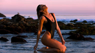 Tashia McIntosh on the beach in a black St Raphael thong swimsuit